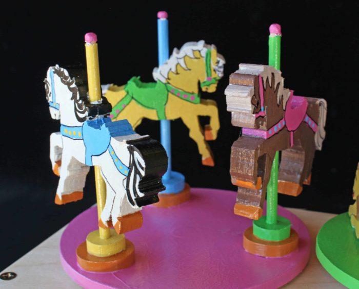 Carousel horses turn around on a cam box