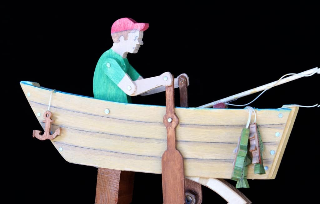 Fun action toy as boy rows the swinging boat home from fishing