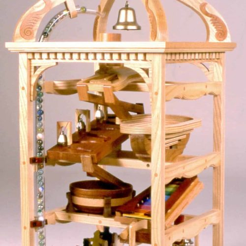 A crank is turned moving marbles to the top then they travel down two pathways