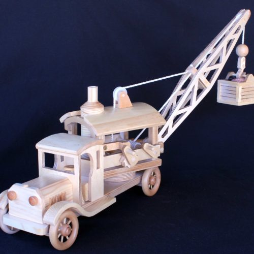 Wood crane with a load of rock. Crane and load can be raised