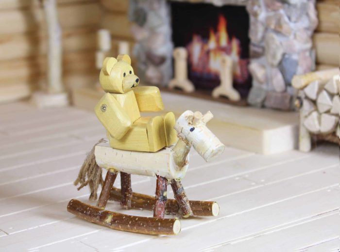 Baby bear rocks on the wood horse in front of the fireplace