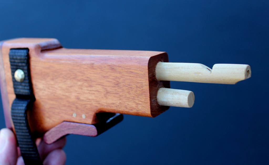 Back of wood weapon showing the built in whistle